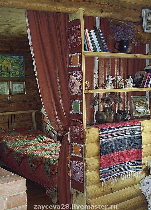 стеллаж, разделяющий комнату на две зоны, украшен оригинальным саше с кармашками для мелочей.