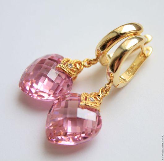 Элегантное украшение, выполненное в классическом стиле – маленькие серьги из цирконов в виде розовых ограненных сердечек в высококлассной, покрытой золотом фурнитуре.
