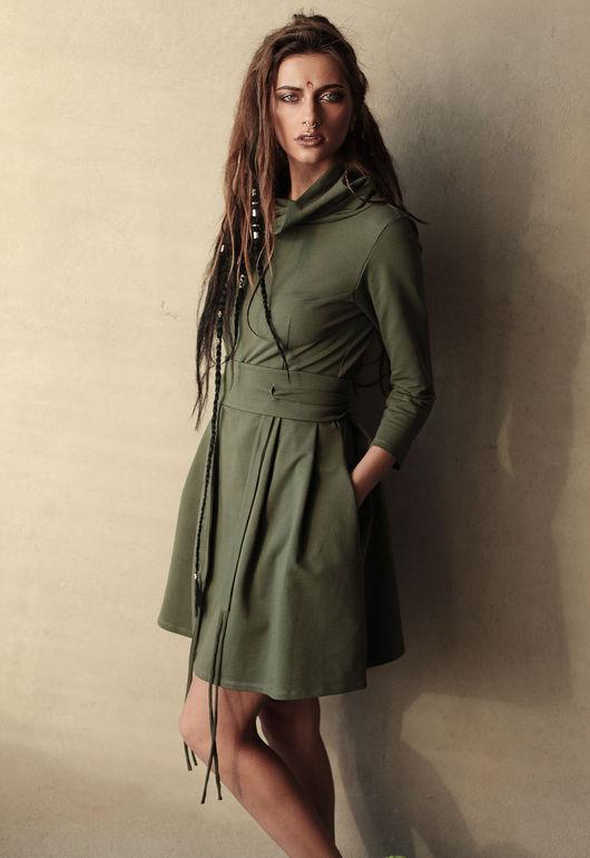 Платье имеет укороченный силуэт, мягкий воротник стойку. Крупные складки от талии создают красивую форму подола. Широкий пояс с тонкими завязками подчеркивает талию.