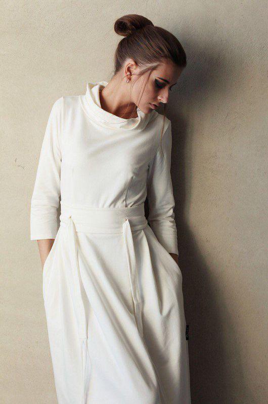 Платье оформлено объемным воротником стойкой, слегка приоткрывающим ключицы, и широким поясом, который в сочетании со слегка завышенной талией подчеркивает достоинства фигуры.