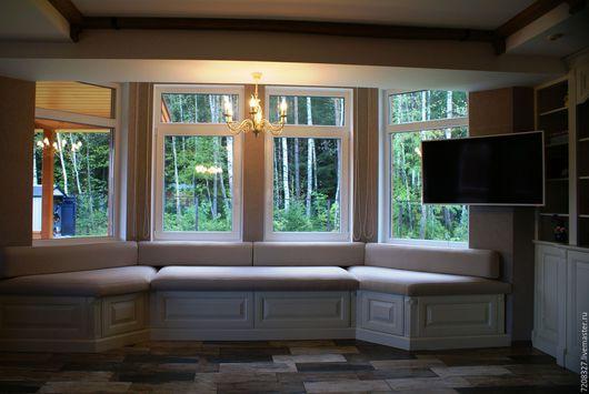 Встроенный в нишу диван-эркер с основанием, выполненном в классическом стиле и мягким матрасом и подушками.