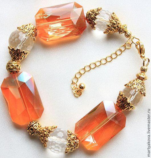 Очень заметный, эффектный, стильный, достаточно крупный браслет из яркого шикарного ограненного стекла персикового (оранжевого) цвета и крупного ограненного горного хрусталя.
