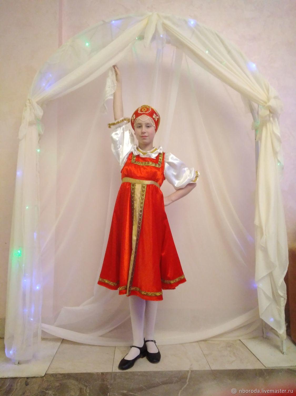 Русский классический костюм: сарафан, сорочка, кокошник, нижняя юбка. Сарафан 3/4 солнца. Украшен орнаментом из тесьмы и вставкой из ткани. Кокошник расшит вручную стразами и искусственным жемчугом.