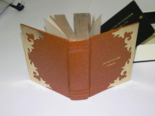 книга в развороте, обрез золоченый,корешок с бинтами, узоры-гравировка по металлу, тиснение наборными шрифтами.