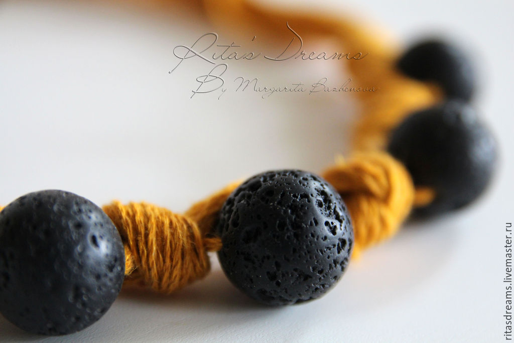 a small light necklace with a large porous black lava beads on a linen thread-mustard color - bright and stylish decoration for the summer.