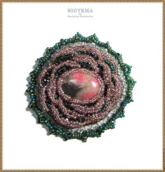 Брошь с родонитом. Выполнена в технике вышивка: бисером и хрустальными бусинами. По центру расположен натуральный камень родонит. Брошь-роза объемная и сверкает зелеными гранями из под пепельно-розовы
