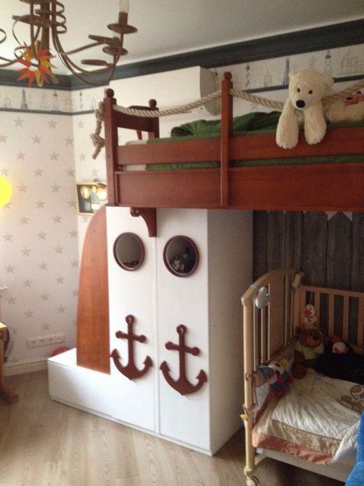 Кровать-чердак в морском стиле с декоративными элементами в виде якоря, штурвала, канатов. Её по достоинству оценят маленькие искатели приключений.