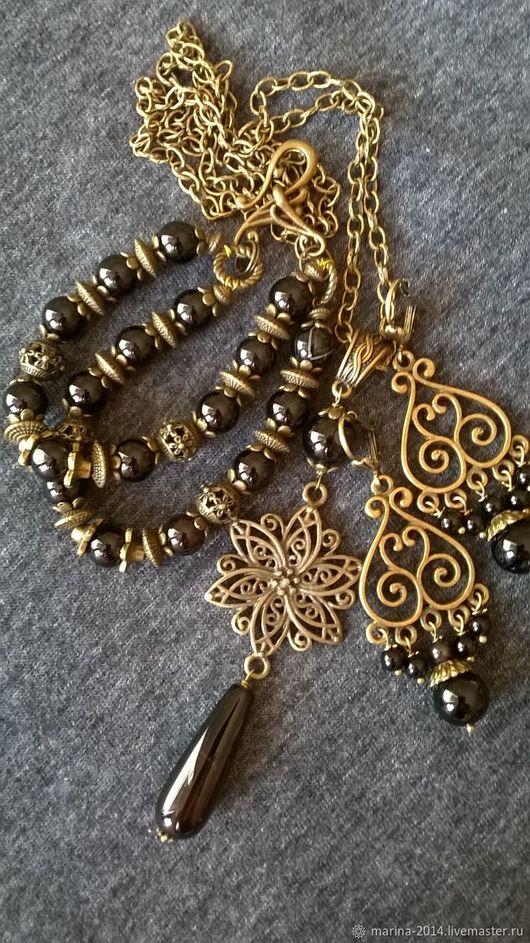 Стильный комплект украшений с чёрным агатом и ажурной фурнитурой под бронзу: цепь с подвеской, двухрядный браслет и пышные длинные серьги.