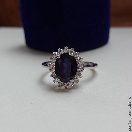 Кольцо с сапфиром и фианитами  в стиле помолвочного кольца принцессы Дианы и Кейт Миддлтон выполнено из серебра 925 пробы. Сапфир темно-синий 8х6 мм.