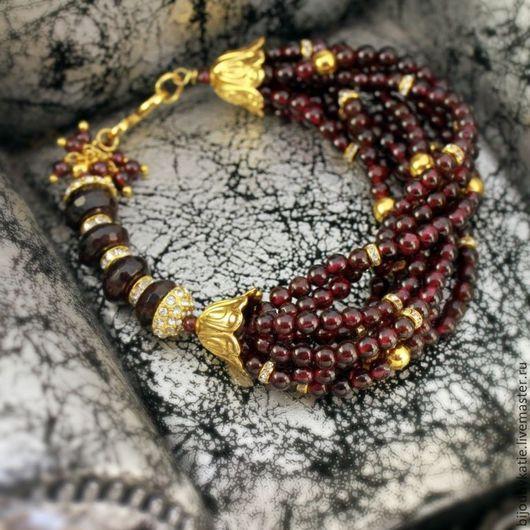 Браслет из бусин натурального камня гранат на ювелирном тросике с металлической фурнитурой под золото с ювелирными стразами